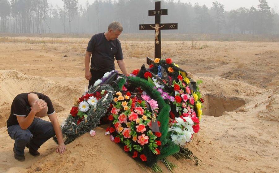 En deuil, le fils (au sol) et le mari de Natalia Ivleva, 47 ans, victime des feux de forêt ravageant la Russie - tombée malade en inhallant de la fumée acre pendant qu'elle tentait d'éteindre les flammes dans le quartier moscovite de Mokhovoye - s'occupent de sa tombe, lors d'une cérémonie dans le village de Beloomut, à 150 kilomètres de la capitale Moscou, hier.