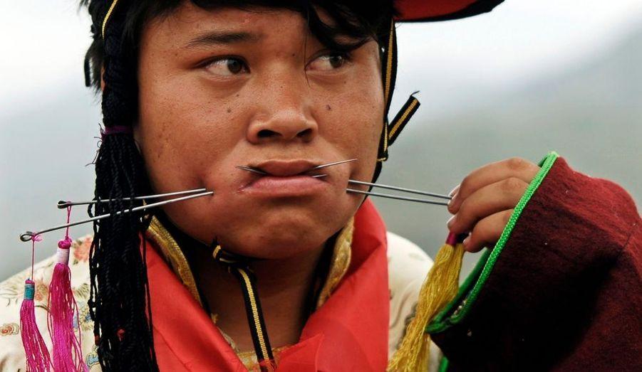 Un tibétain a sa bouche percée d'aiguilles d'acier pendant le festival Lurol à Rebkong, dans la province du Qinghai. Chaque année, cette fête religieuse a lieue pendant le sixième mois du calendrier lunaire tibétain et a pour but de montrer des performances de sacrifice aux dieux qui, selon la légende, rendraient visite aux villageois par l'intermédiaire des médiums.