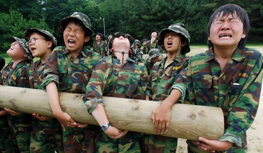 Des étudiants soulèvent un tronc d'arbre dans un camp militaire d'été pour les civils, à Ansan, à environ 80 km de Séoul, visant à se renforcer sur le plan physique et mental.