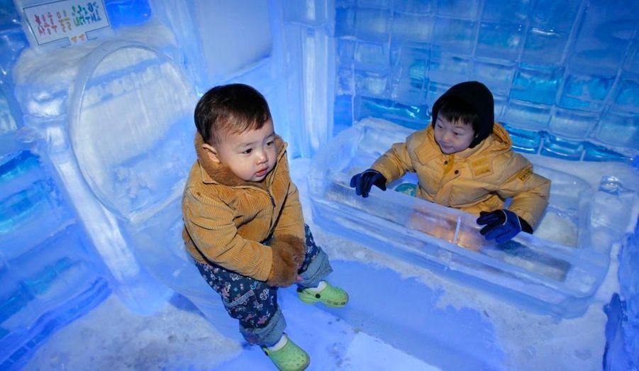 Deux enfants jouent dans une salle de bain appartenant à la Galerie des glaces de Séoul. Le centre national météorologique de Corée du Sud a récemment émis un avertissement de chaleur torride à l'échelle nationale, selon les médias locaux.