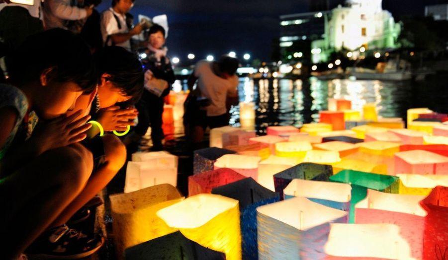 Des jeunes filles japonaises prient après avoir déposé une lanterne colorée sur les bords de la rivière Motoyasu, en souvenir des victimes de la bombe atomique, lors du 65eme anniversaire du bombardement d'Hiroshima, hier.