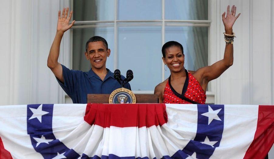 Le président américain Barack Obama et sa femme Michelle saluent depuis leur balcon les familles des militaires venues à un barbecue organisé à la Maison Blanche pour célébrer la Journée de l'Indépendance de l'Amérique.