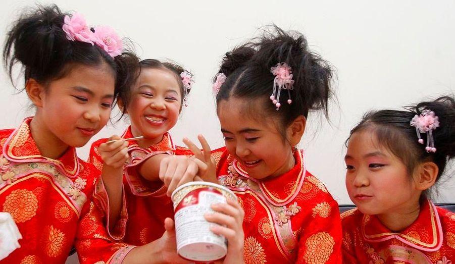 Des petites filles partagent un pot de glace avant de se représenter à l'occasion du 75ème anniversaire du Dalaï Lama, hier à Taïpei.