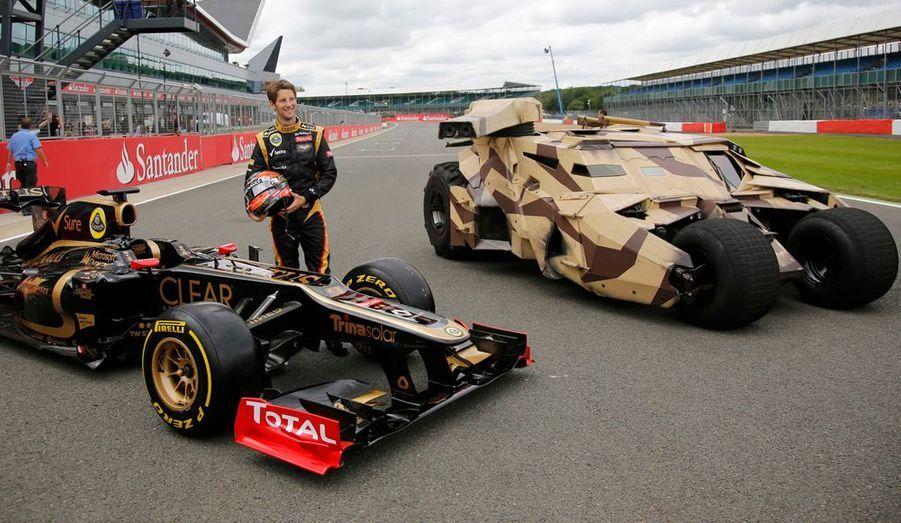 Sur le circuit de Silverstone, en Angleterre, Romain Grosjean prend la pose devant sa Lotus-Renault et le Tumbler, la fameuse Batmobile de Bruce Wayne, pour la promotion du troisième volet de la trilogie Batman mise en scène par Christopher Nolan.