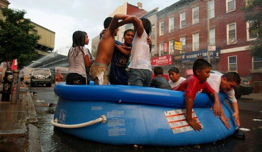 Des enfants se rafraichissent dans une piscine gonflable posée dans l'une des rues du quartier de Brooklyn à New York afin de lutter contre une vague de chaleur qui s'est installée dans la ville.