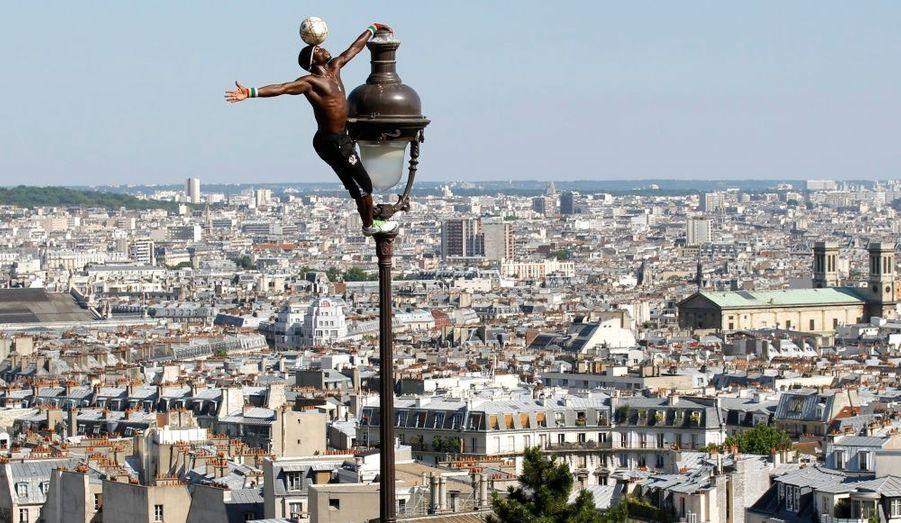 Surplombant la capitale du haut de Montmartre, le footballeur guinéen Iya Traore escalade un lampadaire tout en jonglant avec un ballon dans les jardins de la basilique du Sacré Coeur, sous le soleil dominical du 4 juillet 2010.