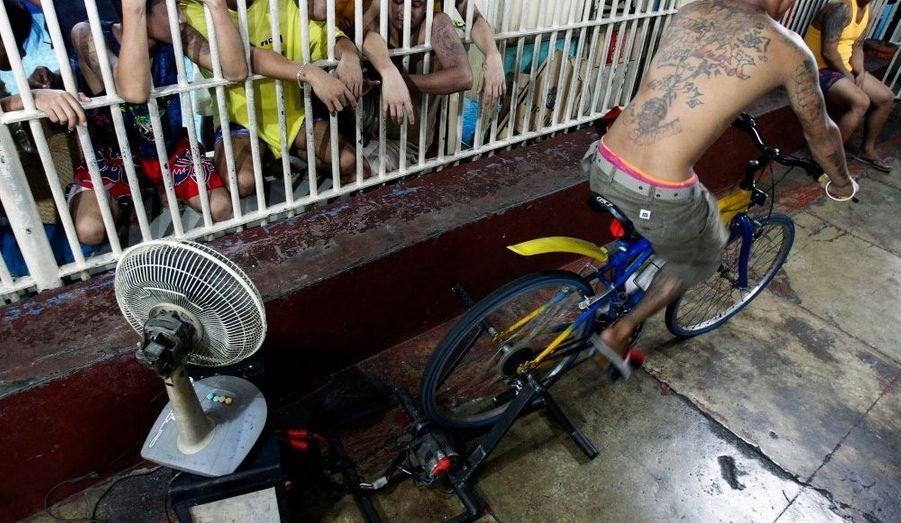 Un détenu pédale sur un vélo fixe relié à une batterie qui a pour but d'alimenter les lampes et les appareils électriques d'une prison de la ville de Makati, à Manille.