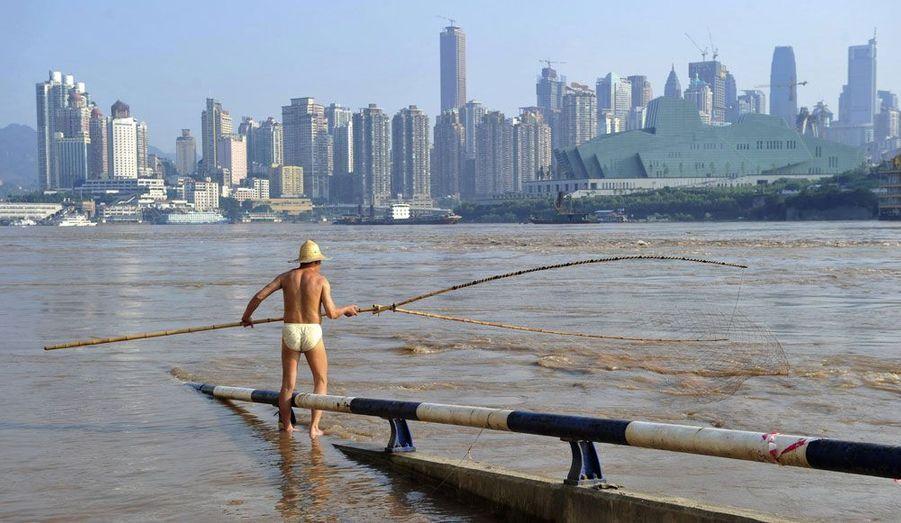 """Un résident de la ville de Chongking """"profite"""" des crues exceptionnelles du Yangsé pour tester son filet de pêche. Les pluies torrentielles qui se sont abattues depuis le 20 juin dernier sur la côte est de la Chine ont déjà fait 50 morts et 42 disparus."""