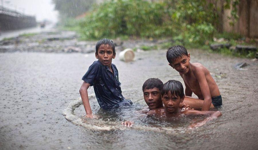 Des petits garçons jouent sous la pluie alors que la mousson a débuté en Inde.