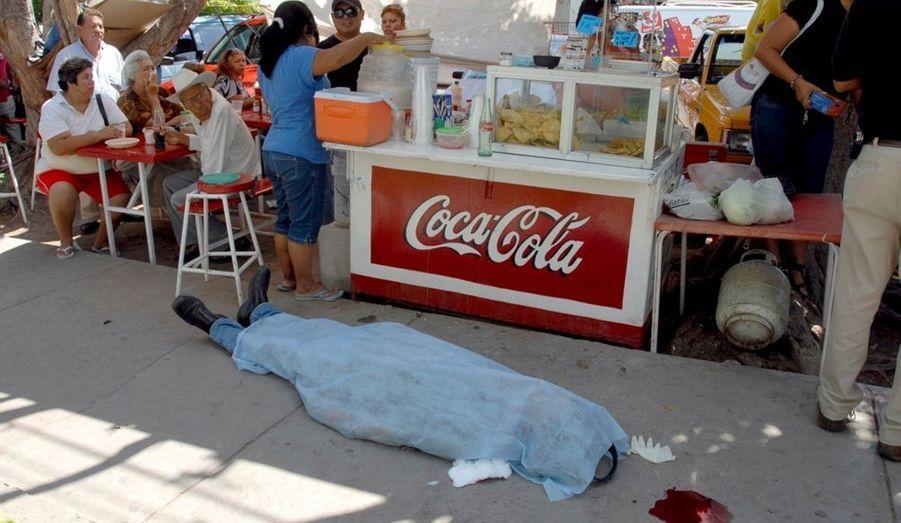 Des clients d'un stand de tacos déjeunent malgré le corps d'un homme gisant sur le trottoir à Ciudad Obregon, au Mexique. D'après les autorités locales, le malheureux aurait succombé à une crise cardiaque.