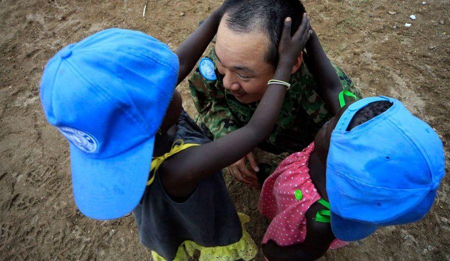 Un casque bleu de l'ONU joue avec deux petites filles dans le CCC (Confident Children out of Conflict), un centre pour enfants protégé des conflits situé à Juba, la capitale du Sud-Soudan.