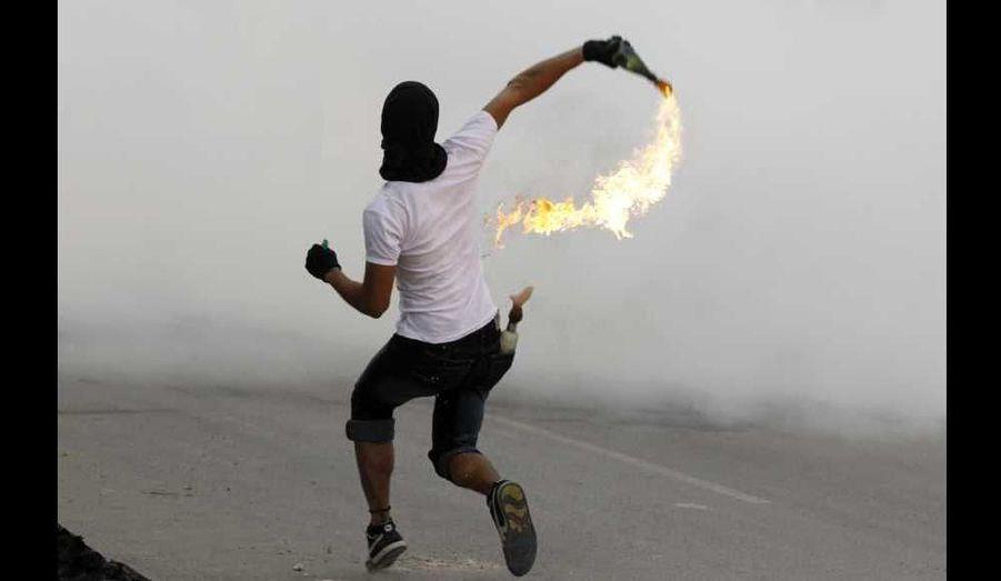 Un manifestant anti-gouvernemental jette un cocktail Molotov sur la police anti-émeute lors d'affrontements en marge du cortège funèbre d'Abdulsamad Ahmed Ismael, tué d'une blessure par balle vendredi matin dans le village de Salmabad, au sud de Manama.