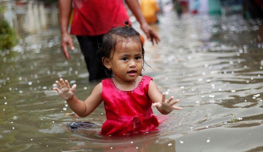 Une petite fille joue dans une rue inondée à Jakarta, conséquence des fortes précipitations de ces derniers jours.