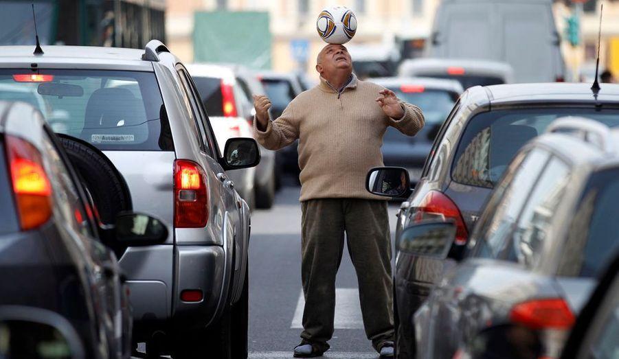 Un homme jongle avec un ballon de foot sur la tête, en pleine circulation à Rome. C'est un habitué, qui divertit les conducteurs qui attendent que le feu passe au vert… et leur demande ensuite une petite contribution.