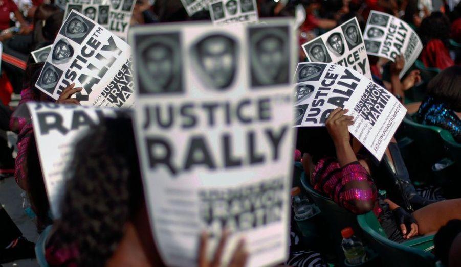 Des manifestants, se protégeant du soleil avec des affichettes, lors d'un rassemblement dans un parc de Miami pour réclamer justice pour Trayvon Martin. Cinq mille personnes se sont mobilisées dimanche pour que soit arrêté le vigile de quartier qui a tué par balles un adolescent noir le 26 février dernier à Sanford.