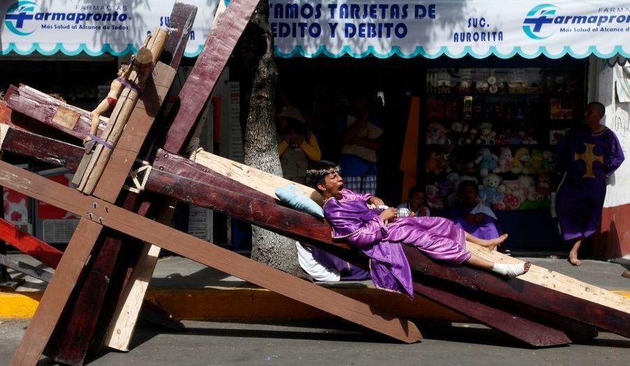 Un pénitent se repose sur une croix, en attendant la procession reconstituant la crucifixion de Jésus-Christ le Vendredi Saint dans le quartier d'Iztapalapa à Mexico.