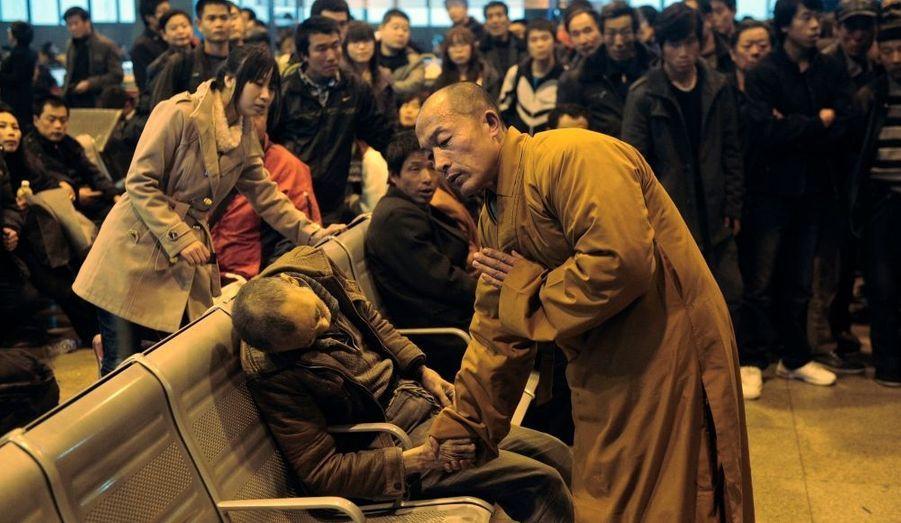 Un moine qui attendait son train, pratique les derniers sacrements en priant pour un homme retrouvé mort dans le hall de la gare de Shanxi Taiyuan, en Chine, le 25 Novembre.