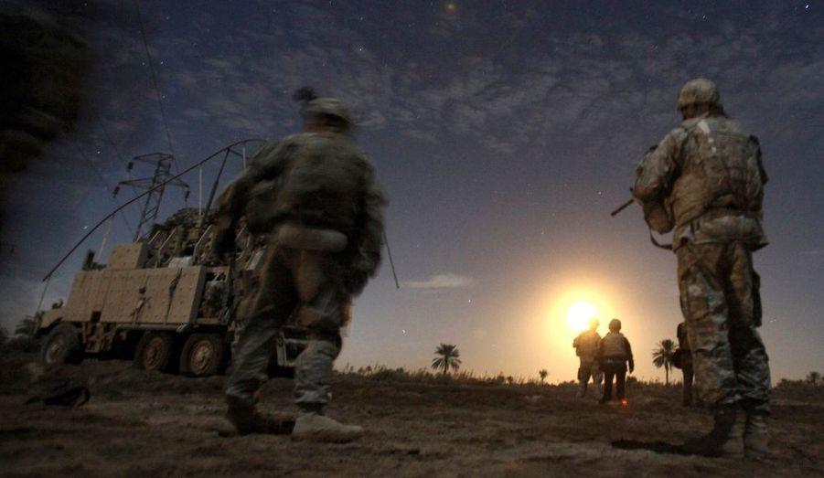 Des soldats américains de la Charlie Company regardent tomber une fusée éclairante lors d'une patrouille de nuit, près du camp Kalsu de Tunis, en Irak.