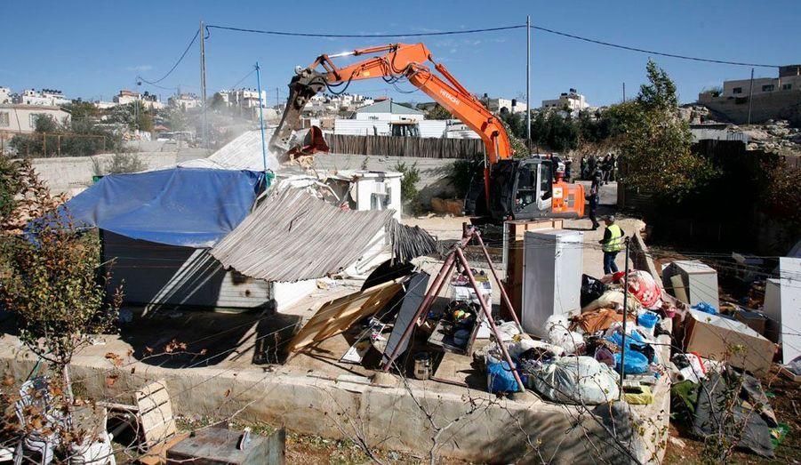Un bulldozer israélien démolit une maison palestinienne àBeit Hanina, à Jérusalem-Est, conformément à la décision du ministère de l'Intérieur. Cet acte fait suite à la décision de construire 800 logements supplémentaire sur ce territoire que l'Etat hébreu se dispute avec l'Autorité palestinienne depuis plus de quarante ans.