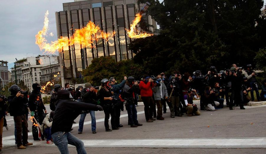 Un manifestant lance un cocktail molotov place Syntagma, à Athènes, mardi. Des casseurs ont rejoint une manifestation commémorative de la mort d'un étudiant en 2008.