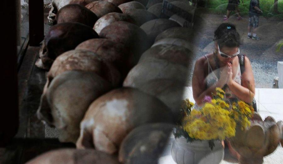 Une touriste prie devant un mémorial contenant les restes de quelque 9000 victimes du régime Khmer rouge à Choeung Ek, un ancien lieu d'exécution et charnier, situé à 17 km au sud-ouest de Phnom Penh (Cambodge).