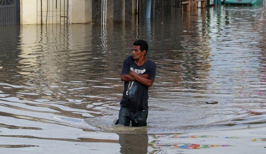 Un homme marche dans une rue inondée à Cali. Conséquence du phénomène climatique La Niña, les pluies torrentielles ont fait au moins 96 victimes ont annoncé les autorités colombiennes.