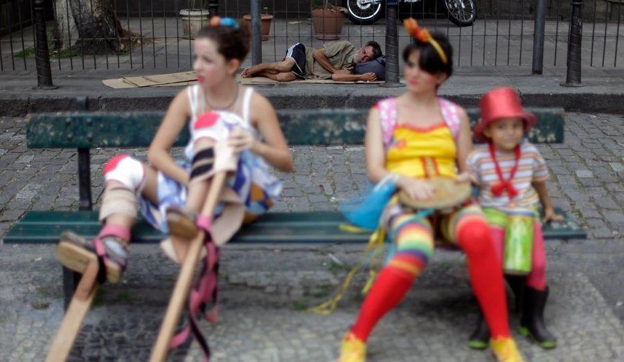 """Un sans-abri dort alors que des fêtards se préparent à assister à une parade à Rio de Janeiro. Le défilé de clowns, avec comme slogan """"Grève des clowns: Comment serait le monde sans rire?"""" s'inscrit dans le cadre d'un festival international qui se déroule à Rio."""