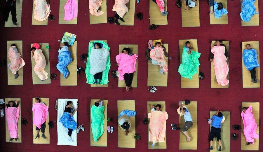 Des parents d'élèves dorment sur des nattes sur le sol d'un gymnase, sur le campus de l'université de Wuhan en Chine. Quelque 400 parents ont pu accompagner leurs enfants, étudiants en première année, pour leur premier jour d'école.