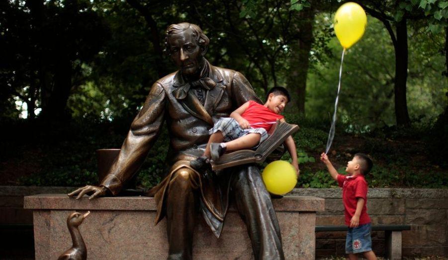 A Central Park (Yew York), deux enfants s'amusent autour de la statue de l'auteur de contes danois Hans Christian Andersen, auteur du Vilain Petit Canard.