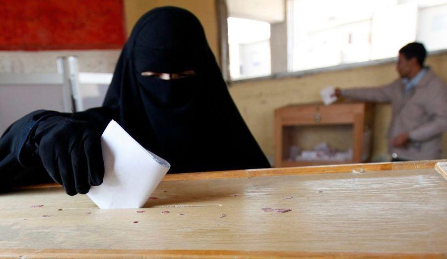 Une femme voilée place son bulletin dans une urne, dans le bureau de vote du gouvernorat d'El-Kalubia à 25 km au nord-est du Caire. Les Égyptiens votent ce mardi pour la troisième phase des élections législatives.