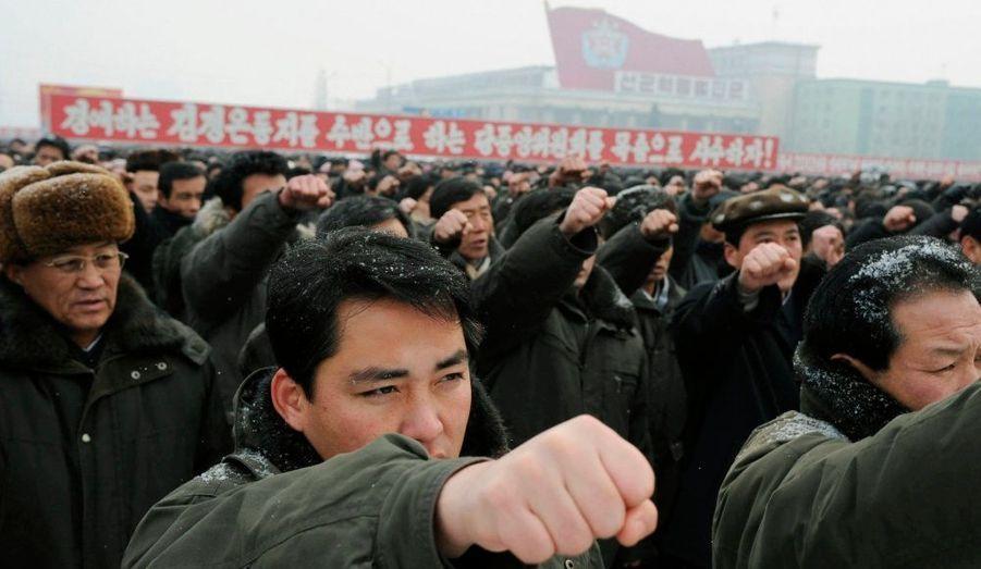 Des Nord-Coréens lèvent leur poing alors qu'ils participent à un rassemblement au square Kim Il-Sung à Pyongyang.