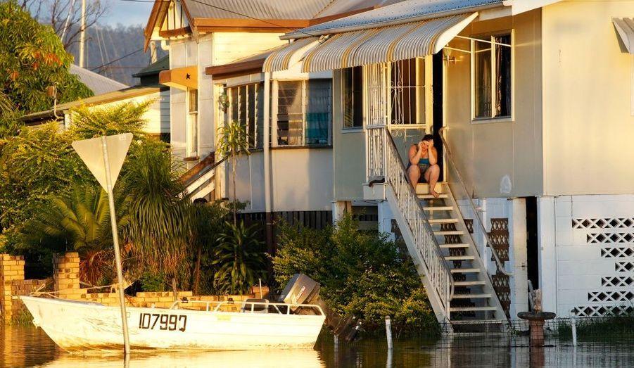 A Rockhampton, une femme tente de joindre ses proches avec son téléphone portable, sa maison étant submergée par les eaux. Les habitants du Nord-Est du Queensland se préparent ce mercredi à une nouvelle montée des eaux, annoncée par les services météorologiques nationaux.