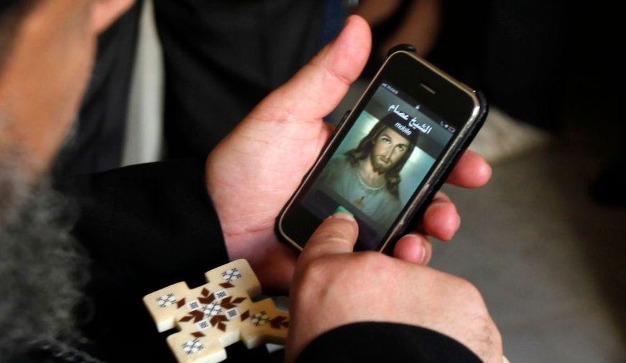 A Alexandrie, ce prêtre copte se sert de son iPhone avant de procéder à une prière pour les proches des victimes qui ont péri après l'attaque à la bombe. 21 personnes sont décédées samedi devant une église de la ville. D'après une source, sept personnes seraient interrogées.
