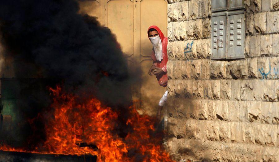 Un jeune Palestinien armé de pierres guette les forces israéliennes, dans un village près de Jénine, en Cisjordanie.