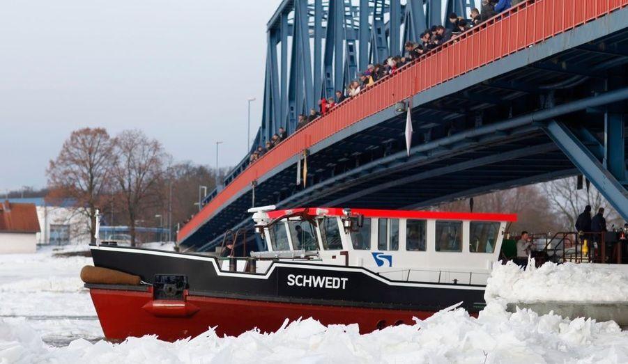 Des passants regardent un Brise-glace sur la rivière Oder à Schwedt, à la frontière de la Pologne. Le niveau du cours d'eau est critique, les températures s'étant radoucies dans la région.