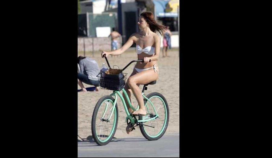 Une jeune femme fait du vélo sur la plage de Santa Monica alors que la température flirte avec les 30 degrés à Los Angeles, un record en cette saison.