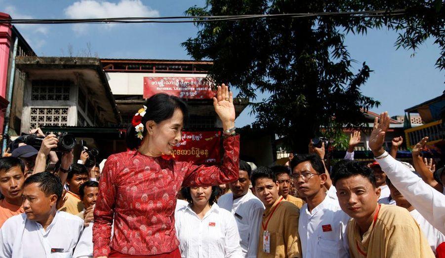 La leader de l'opposition pro-démocratique birmane, la prix Nobel de la Paix, Aung San Suu Kyi, salue ses partisans alors qu'elle quitte les locaux de sa formation politique, la Ligue nationale pour la démocratie où elle a assisté à une cérémonie marquant le 64e anniversaire de l'indépendance du pays.