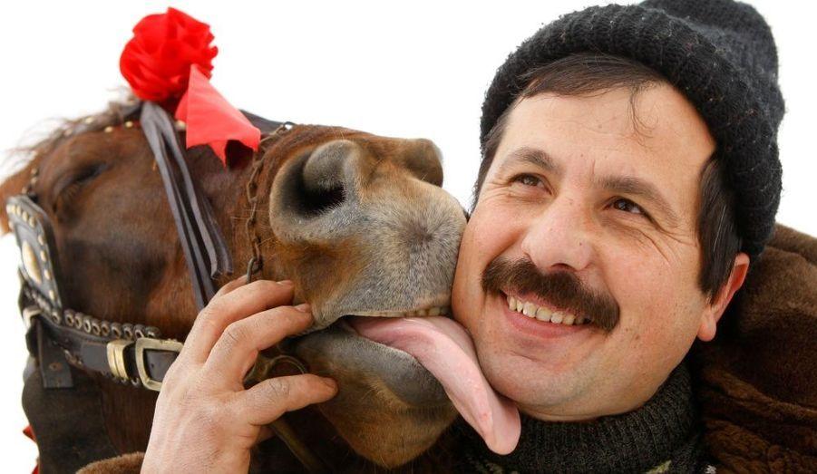 Un cheval lèche son propriétaire après la traditionnelle course de chevaux organisée dans le village de Piertrosani, en Roumanie. L'épiphanie marque, le 6 janvier, la fin des célébrations de Noël en Roumanie.