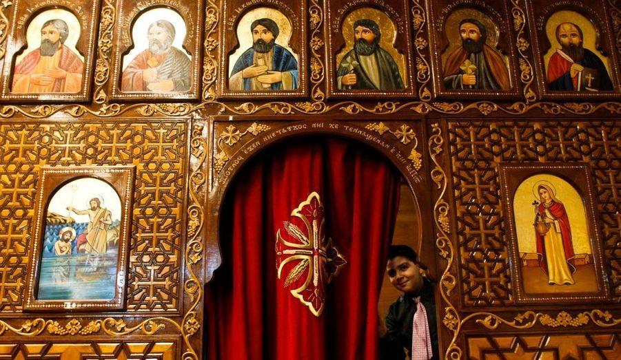 Un petit garçon ouvre un rideau de l'église copte de Francfort durant la messe de Noël. Les chrétiens coptes du monde entier sont en deuil après les attentats qui ont touché leur communauté en Egypte la semaine dernière.