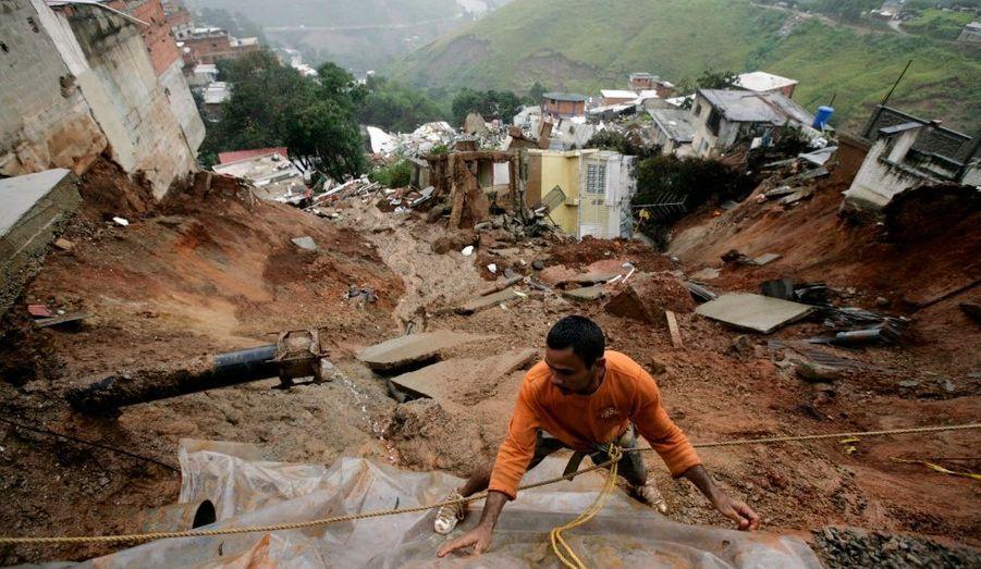 Un habitant de Caracas (Venezuela) tente d'empêcher les infiltrations d'eau en recouvrant de plastique la terre, après un glissement de terrain dans le quartier d'Altavista.