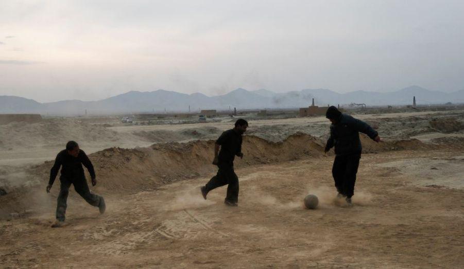 Des ouvriers d'une briqueterie, près de Kaboul, en Afghanistan, se détendent avec une partie de football pendant leur pause.