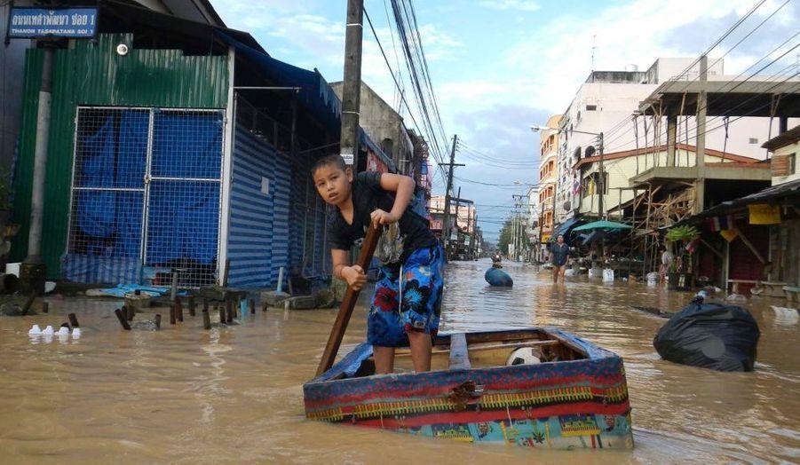 Un garçon utilise un radeau de fortune pour circuler à travers les rues inondées de Had Yai, dans la province de Songkhla, en Thaïlande.