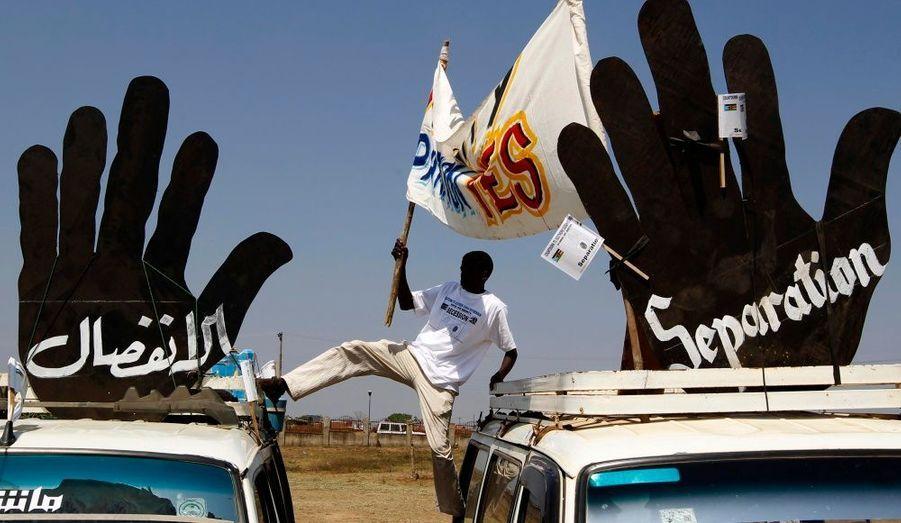 Un homme, en faveur de l'indépendance du Sud-Soudan, brandit une bannière lors d'une manifestation à Juba, la capitale. Il y a de fortes chances pour que le choix de la partition du pays l'emporte lors du referendum du 9 janvier prochain.