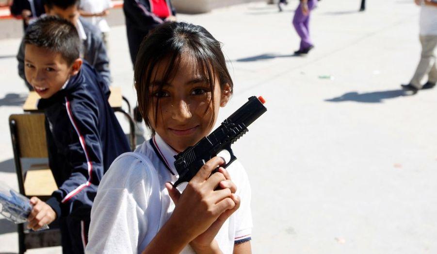 Une fillette pose avec un pistolet en plastique, dans la cour de son école de Ciudad Juarez. Les enfants d'établissements scolaires de la ville la plus meurtrière au monde s'était vu offrir de pouvoir échanger leurs fausses armes contre d'autres jouets non-violents ou des bonbons à l'occasion du Festival des Enfants pour la Paix.