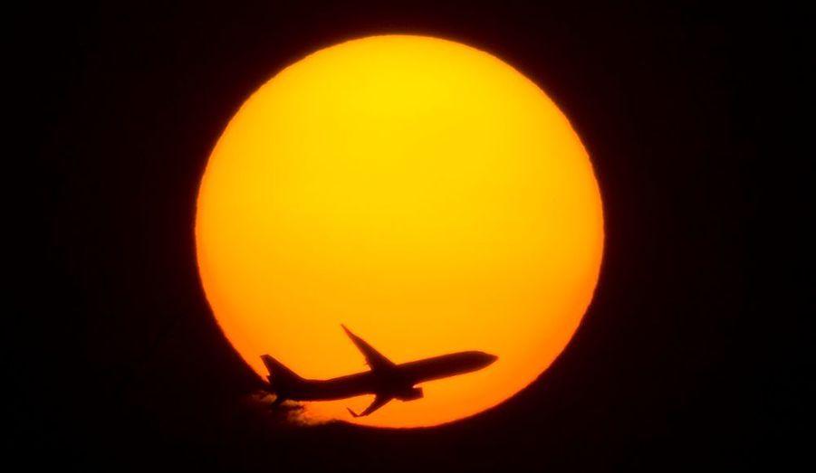 Un avion passe devant le coucher du soleil ici à Shangai.
