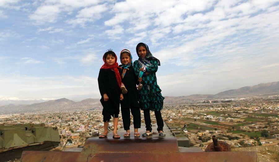 Trois fillettes posent sur la carcasse d'un blindé sur la colline de Wazir Akbar Khan à Kaboul.