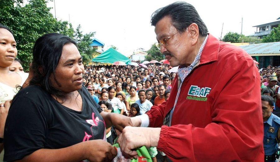 L'ancien président philippin Joseph Estrada distribue de l'aide à une victime au typhon dans les bidonvilles de Baseco, à Tondo.