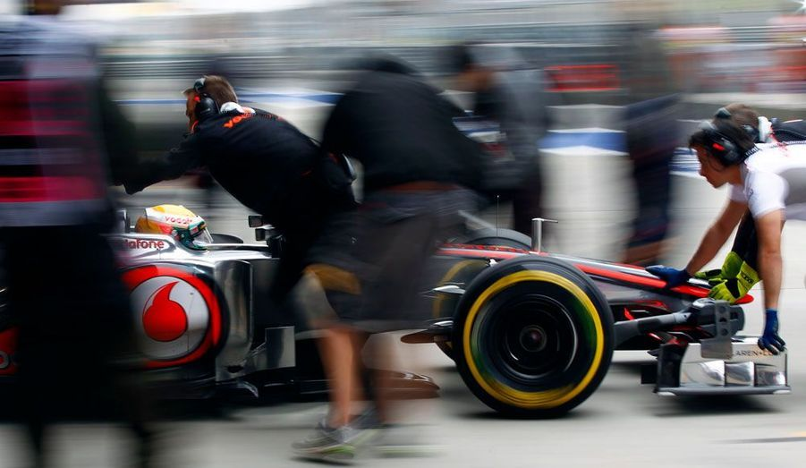 La F1 de Lewis Hamilton est conduite au garage, vendredi, à Shanghai. Le pilote MacLaren participe aux essais en vue du grand prix de Chine, dimanche.