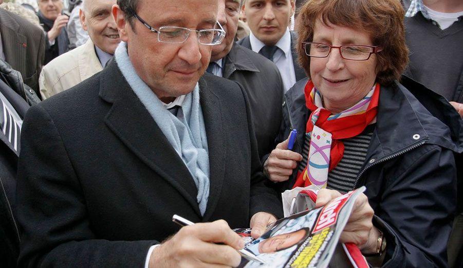 Une lectrice de Paris Match fait dédicacer le numéro du 5 avril par François Hollande à Besançon, mardi.