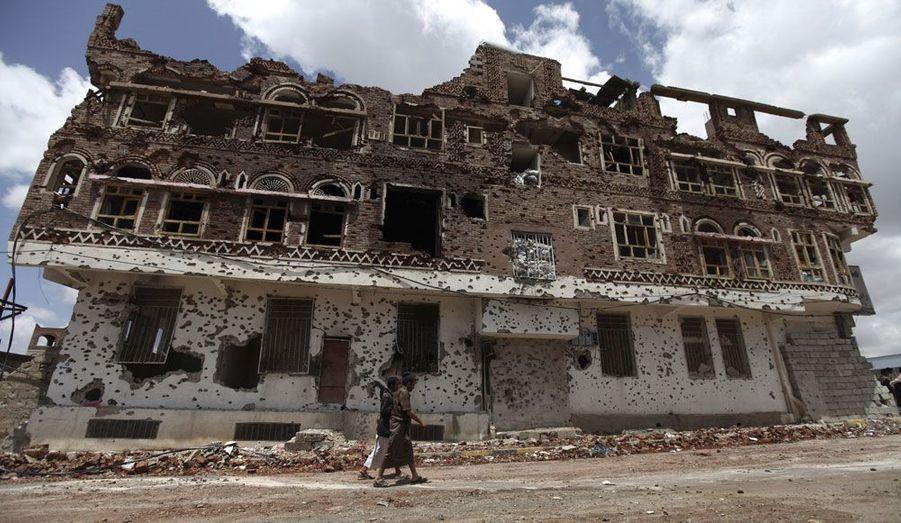 Deux combattants de la tribu Hashed, menée par le chef Sadiq al-Ahmar, marchent à Sanaa, au Yémen, devant un bâtiment criblé de balles.